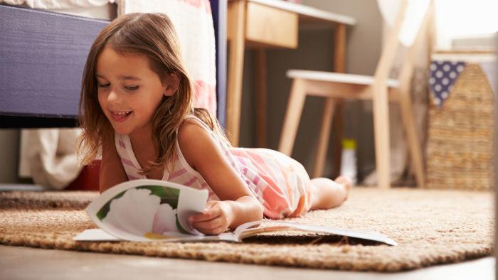 Little girl reading book on floor