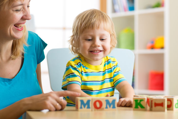 Little boy and his mother playing with letter blocks