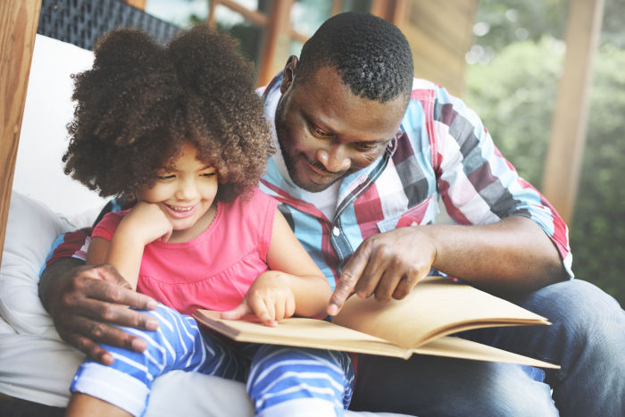 African American father and daughter reading book together