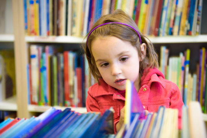 Little girl looking through library books