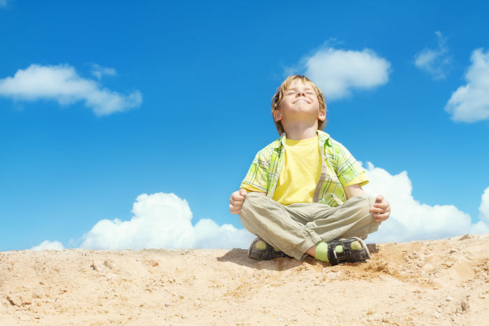Little boy practicing yoga in the sand