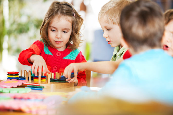 Little boys and girls sharing wooden toys