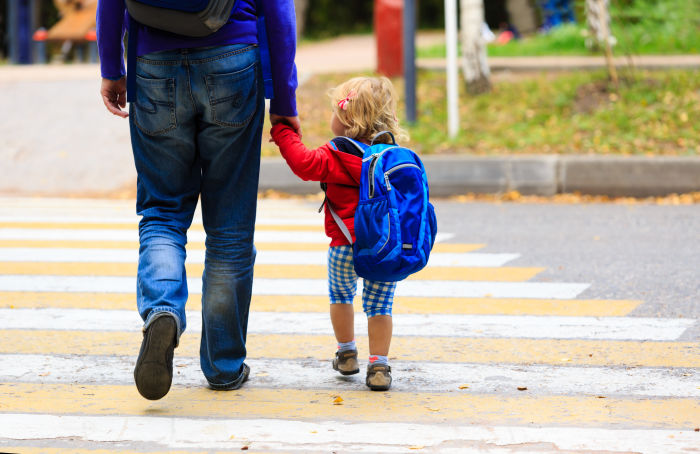 Little girl crossing street while holding father's hand