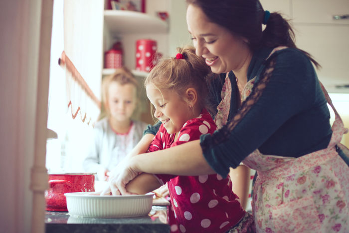2 little girls cooking with their mother